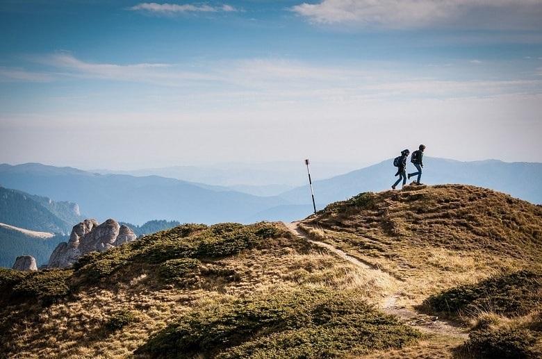 Zwei Wanderer in einer schönen Landschaft. Symbolbild für die Frage nach dem einfachen Glück mit wenig Geld.