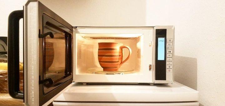Eine Tontasse in einer Mikrowelle. Symbolbild für die Erklärung, wie eine Mikrowelle funktioniert und warum man mit Tontassen vorsichtig sein muss.